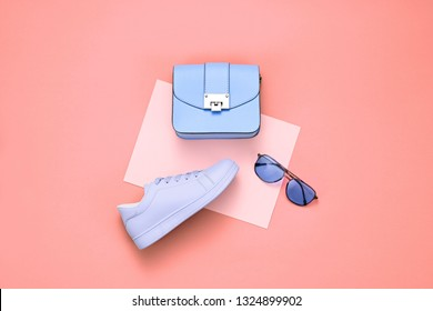 Spring summer Girl Outfit. Woman Accessories Set. Minimal Creative Hipster art Flat lay on coral. Fashion sneakers shoes, Trendy purple Handbag, Glamour blue fashionable Sunglasses