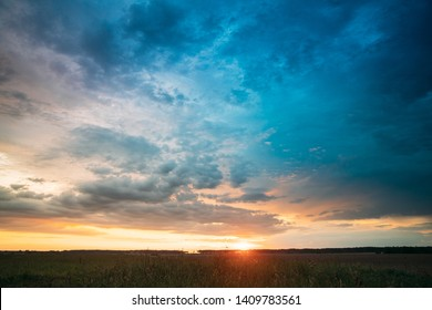 Spring Summer Meadow At Evening Sunset Sunrise. Natural Bright Dramatic Sky In Different Colours Above Countryside Meadow Landscape. Agricultural Landscape In May.