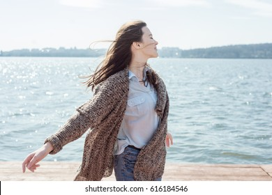 Spring or summer portrait of a beautiful young woman smiling happy student outdoor sea or ocean or lake