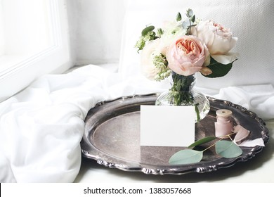 Spring, summer still life scene.Blank place card mockup on old silver tray at windowsill. Vintage wedding  feminine styled photo, floral composition. Bouquet of pink English roses and Ranunculus.