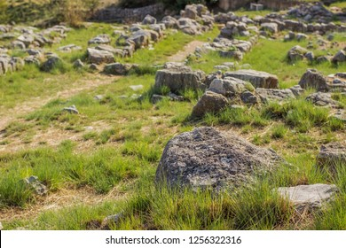 spring sunny bright highland meadow with green grass small ground trail and many stones and rocks country side landmark landscape