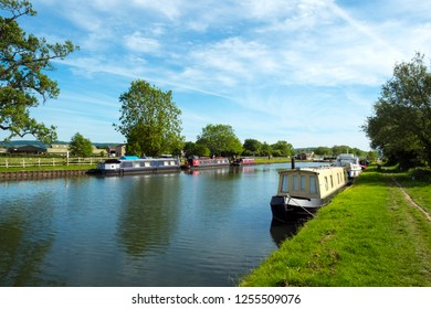 Spring sunshine on boats moored by St Marys Church on the Gloucester & Sharpness Canal, Frampton on Severn, Gloucestershire, UK