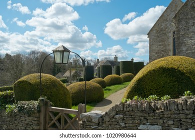 Spring sunshine on the picturesque old churchyard at Duntisbourne Abbots in the Cotswolds, Gloucestershire, UK