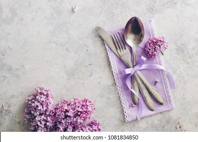 Spring table decoration with lilac flowers. Elegant table setting with lilac flowers, purple napkin  and vintage silverware on rustic background.