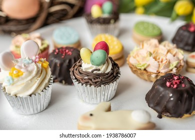 spring table setting easter egg  cake cupcake, muffin, chocolate tartlet icing treat with fresh flowers yellow tupils