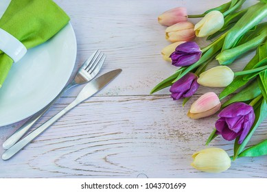 Spring table setting with purple and pink tulips