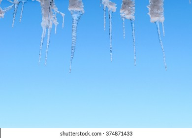 Spring thaw, ice icicles on blue sky background.