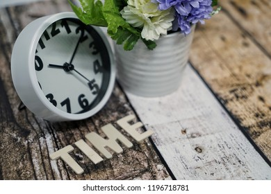 spring time with alarm clock and statice flowers bouquet background. Selective focus.