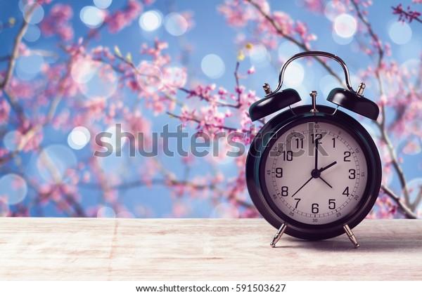 Concept de changement d'heure du printemps avec réveil sur fond nature fleur d'arbre
