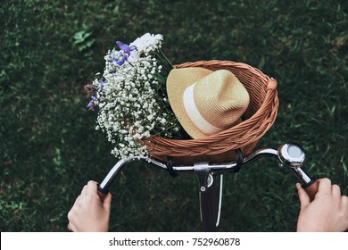 Spring time! Close-up of woman riding on a bicycle with flowers and a hat in the basket
