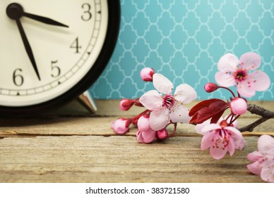 Spring Time / Pink Blossoms and an Alarm Clock on an Old Wooden Table