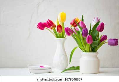 Spring tulips bouquets in white beautiful vases