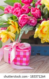 spring tulips and daffodil flowers with gift box