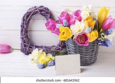 Spring tulips, daffodils flowers in grey bucket, decorative heart  and empty tag on  white wooden background. Selective focus. Place for text.