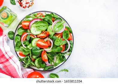 Spring vegan salad with spinach, cherry tomatoes, corn salad, baby spinach, cucumber and red onion. Healthy food concept. Gray stone table. Top view. Copy space
