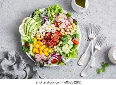 Spring vegetable salad with chickpeas, avocado and feta. Tasty healthy food. Buddha bowl. On a gray background, top view