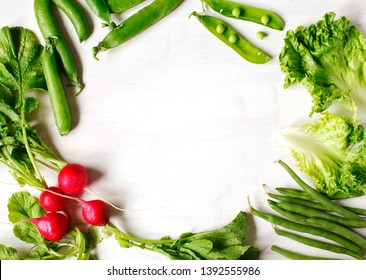 Spring vegetables on white wooden background with copy space. Radish, green peas, green beans and green salad - fresh harvest from the garden. Copy space, copy space