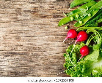 Spring vegetables on wooden background with copy space. Radish, green peas and green salad - fresh harvest from the garden. Copy space.
