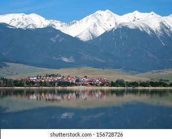 Spring view of small village named Liptovsky Trnovec located under huge snowy hills of Rohace mountains partially mirrored in deep waters of Liptovska Mara lake.