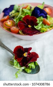 Spring vitamin salad: greens with cherry tomatoes and edible flowers (Pansy) on a light background. The concept of healthy eating.