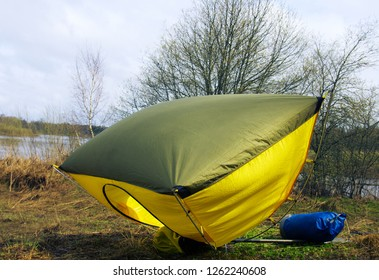 Spring wind flurry. A gust of Wind overturned the open tent on the Bank of the forest river
