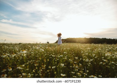 In spring, a young red-haired woman with a floral wreath on her head and in a white dress runing in a field on the grass