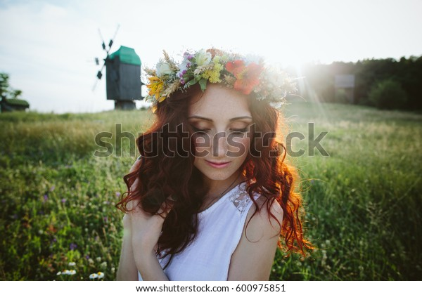 In spring, a young red-haired woman with a floral wreath on her head and in a white dress posing in a field on the grass and rests in sunset lights