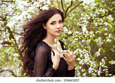 Spring - young woman under blossom tree