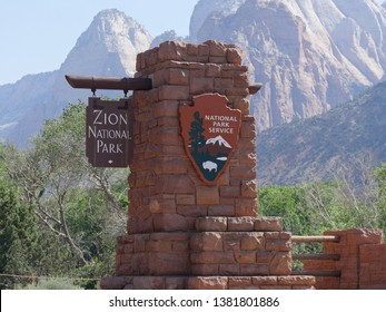 Springdale, Utah, USA--July 2018: Portrait cropped shot of the red brick gate with sign to Zion National Park at the Springdale entrance, Zion National Park in Utah, USA.