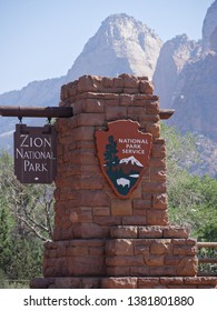 Springdale, Utah, USA--July 2018: Red brick gate with sign to Zion National Park at the Springdale entrance, Zion National Park in Utah, USA.