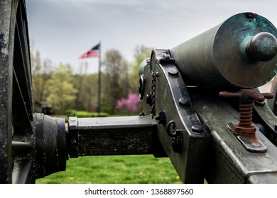 Springfield, MO—April 11, 2019; bronze civil war era confederate cannon points toward American flag at Wilsons Creek National Battlefield in southwest Missouri in spring