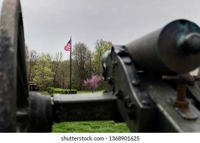 Springfield, MO—April 11, 2019; bronze civil war era confederate cannon points toward American flag in focus at Wilsons Creek National Battlefield in southwest Missouri in spring