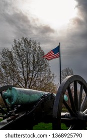Springfield, MO—April 11, 2019; bronze civil war era confederate cannon points past American flag at Wilsons Creek National Battlefield in southwest Missouri with sunlight breaking through clouds