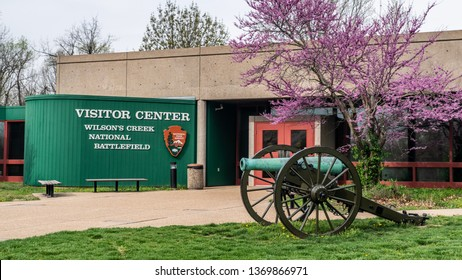 Springfield, MO—April 11, 2019, bronze civil war era cannon sits in front of the visitor center entrance at Wilsons Creek National Battlefield with flowering purple tree in spring
