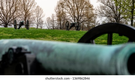 Springfield, MO—April 11, 2019; two civil war era cannons on hill top with bronze barrel of another blurred in foreground at Wilsons Creek National Battlefield park in spring.