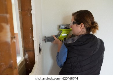 SPRINGFIELD, OR - DECEMBER 20, 2017: Female construction worker and homeowner using a sawsall tool to cut drywall out and take a wall down to a half-wall during a DIY house renovation.