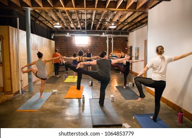 SPRINGFIELD, OR - MARCH 11, 2018: Intermediate students practing poses during a class at Common Bond Yoga, an urban yoga startup company located in downtown Springfield.