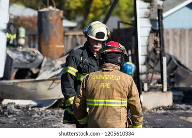 Springfield, OR - October 17, 2018: Eugene and Springfield fire fighters discuss a course of action in Springfield where a gunman lit homes on fire and then shot a gun at the first responders.