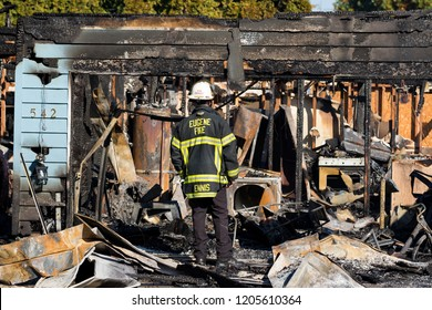 Springfield, OR - October 17, 2018: Eugene Fire Department chief Ennis assesses damages to a home after a gunman lit multiple homes on fire and then shot at first responders in Springfield Oregon.