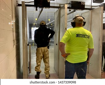Springfield, OH- June 22, 2019: Firearms instructor watches trainee in shooting lane at OPOTA requalification class. Student drawing from holster at indoor shooting range. Concrete wall and bullet