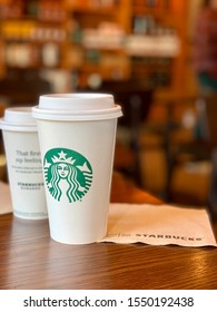 Springfield, PA - November 3, 2019: Starbucks coffee cup in store. A grande sized Starbucks branded coffee cup rests on a table in a Starbucks store.