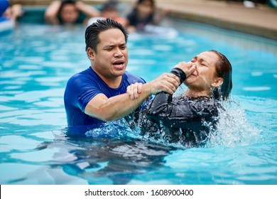 Springfield, VA / USA - May 14, 2017:  A preacher baptizes a Christian believer after making her decision to follow Jesus Christ through water baptism.