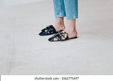 spring/summer outfit fashion details, young stylish woman wearing denim jeans and floral mules with a bow detail in front. urban fashion blogger posing outdoors, street style.