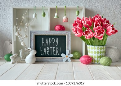 "Springtime background with Easter decorations, tulips and a chalk board. Text ""Happy Easter"" on the board"