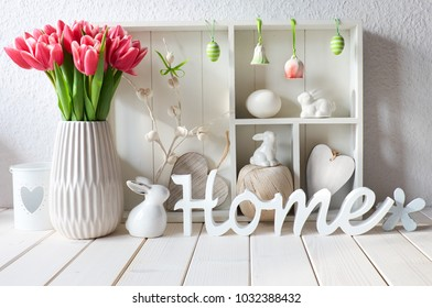 """Springtime background with spring decorations. Display cabinet with different objects and pink tulips. Word  """"Home"""" made of wood."""
