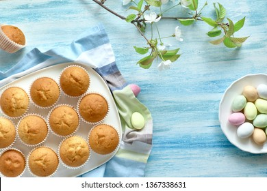 Springtime or Easter flat lay with plate of lemon muffins and marzipan eggs on light blue background with fresh apple flowers