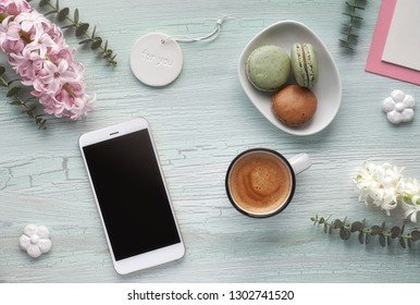 Springtime flat lay with coffe, macarons, pearl hyacinth flowers, eucalyptus, mobile phone and gift postcards