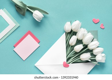 Springtime flat lay, white tulips in paper envelope on green mint background with envelopes, cards and decorative hearts. Geometris background with copy-space.