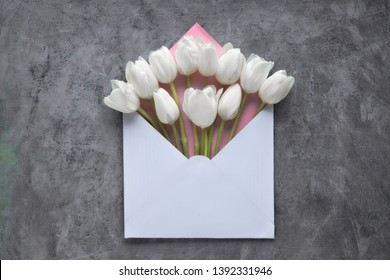Springtime flat lay, white tulips in  envelope on dark textured background, copy-space