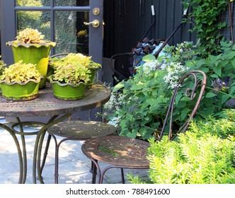 Springtime garden with patio furniture and potted perennials.